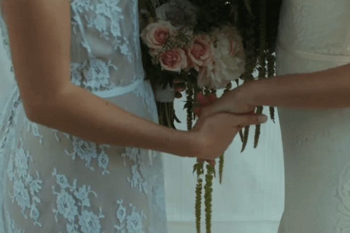 2 brides holding hands