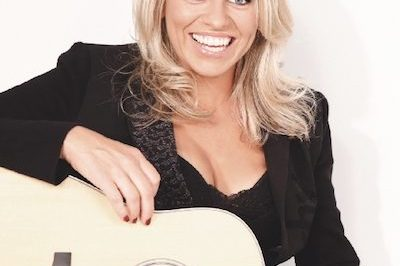Beccy Cole in black top and guitar