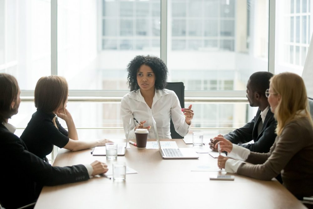Woman of colour sitting at head of boardroom table talking