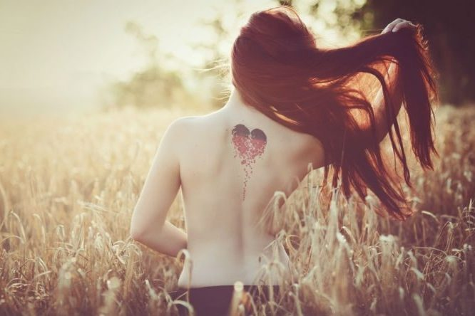 woman from behind with love heart tatoo on her back