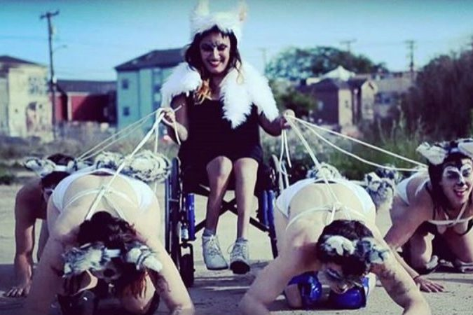 Woman in a wheelchair being pulled by 4 other women
