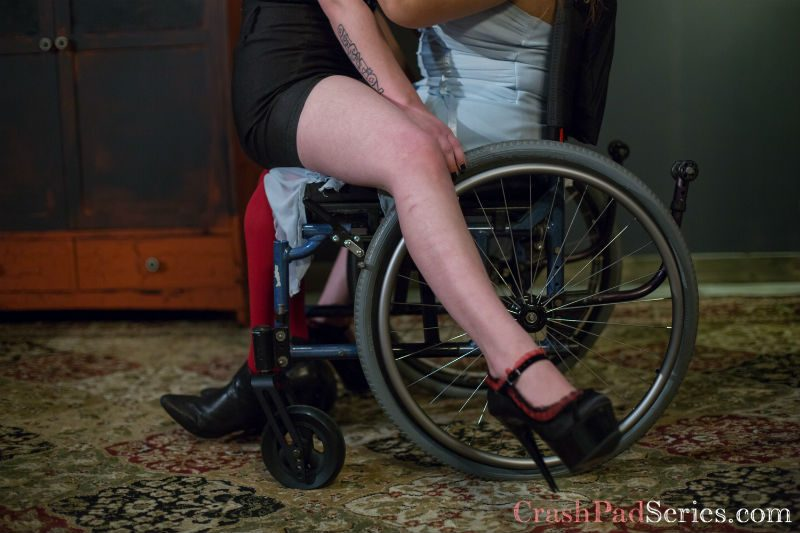 woman sitting on lap of a woman in a wheelchair