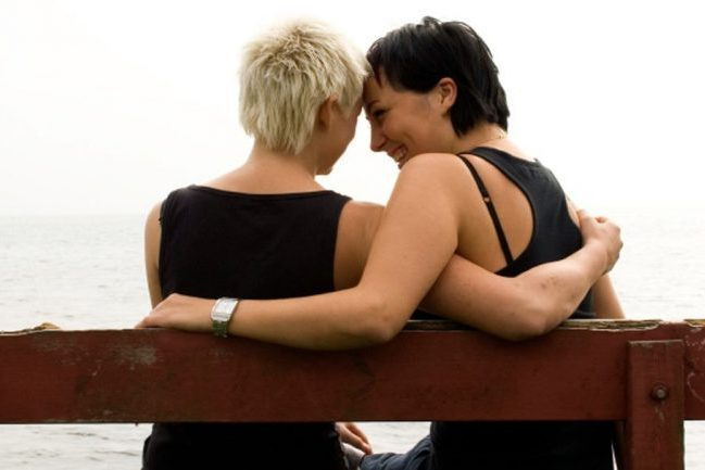 2 women sitting on bench by the water