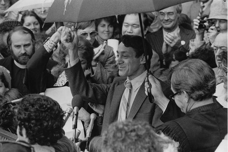 Harvey Milk surounded by people