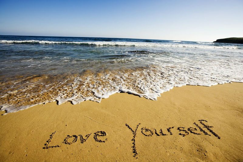 Words written into the sand 'Love Yourself'