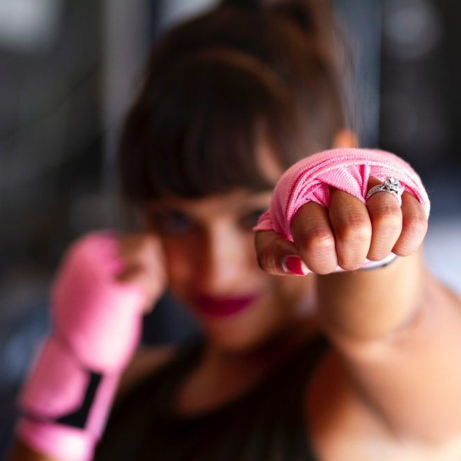 Woman in boxing position with pink gloves